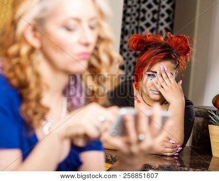 Daughter Looks On As Mother Snoops Through Her Phone