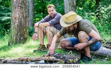 Masculinity concept. How to build bonfire outdoors. Men on vacation. Man brutal bearded hipster prepares bonfire in forest. Arrange the woods twigs or wood sticks. Ultimate guide to bonfires poster