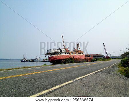 Marie Joseph, Nova Scotia - July 26th, 2014: An Abandoned Ship Lays Rusting Along The Side Of Road O