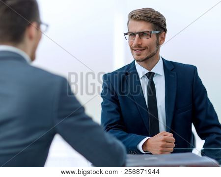 business partners talk sitting at a Desk