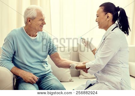 Friendly Looking Nurse Vaccinating Cheerful Retired Man