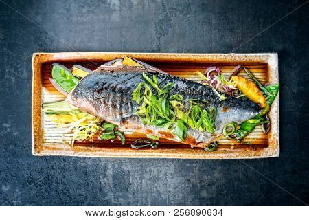 Modern style Japanese bonito tuna fish filet with vegetable and pineapple glazed in teriyaki sauce as top view on a plate  poster