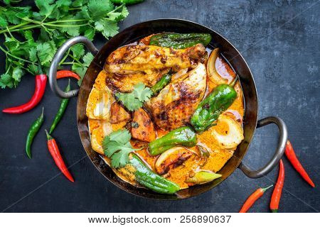 Traditional Thai kaeng massaman coconut chicken curry with jalapeno, poblano chili and sweet potatoes as closeup in a traditional bowl