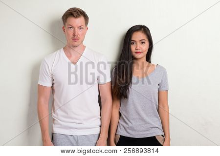 Studio Shot Of Young Multi-ethnic Couple Standing Together
