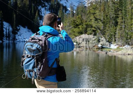 Hiker tourist with backpack taking photo with smartphone near Bear Lake at autumn in Rocky Mountain National Park. Colorado, USA.