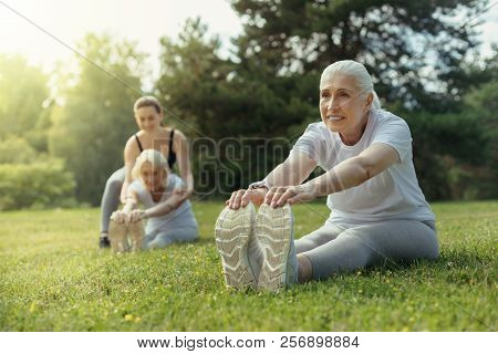 Positive Minded Elderly Woman Doing Stretching Exercise
