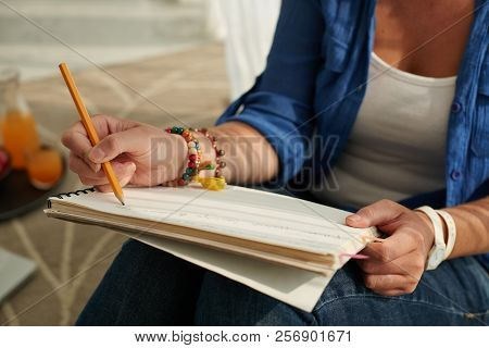 Cropped Image Of Student Writing Essay Or Some Thought In Textbook