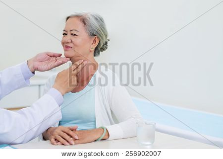 Doctor Checking Thyroid Gland Of Elderly Vietnamese Woman