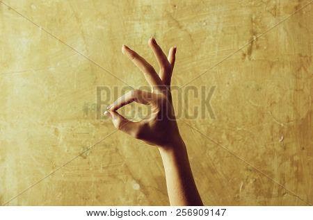 Female Hand Showing Ok Gesture On Abstract Cement Wall On Beige Background. Nonverbal Communication,