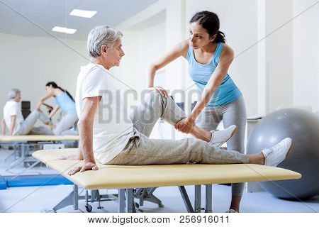 Calm Attentive Medical Worker Warming The Injured Muscles Of Her Patient