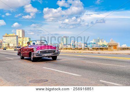 HAVANA,CUBA - AUGUST 12,2018 : Classic convertible car on the famous Malecon seaside avenue in Havana