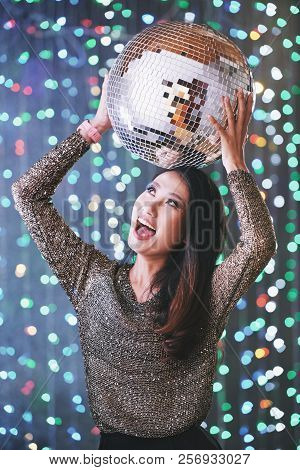 Portrait Of Excited Happy Young Woman Posing With Discoball