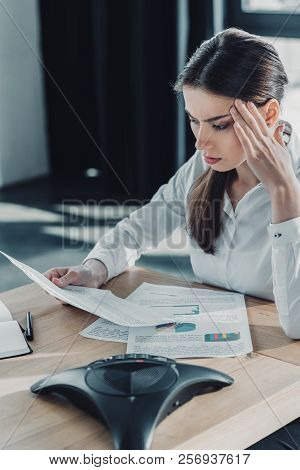 Confused Young Businesswoman Doing Paperwork At Modern Office