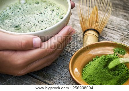 Girl's Hands Holding Matcha Tea In Special Traditional Japanese Matcha Tea Bowl With Bamboo Spoon An