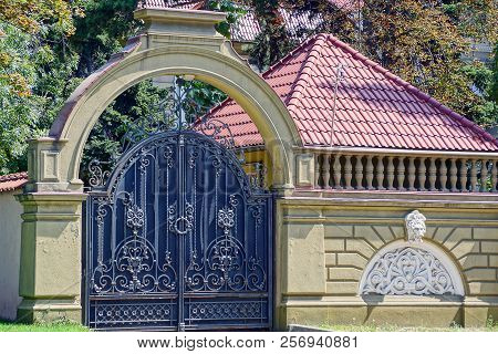 Large Black Iron Gate With A Forged Pattern And A Brown Concrete Fence