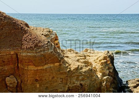 Big Brown Rock On A Background Of Sea Waves And Blue Sky