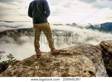 Landscape Photograper With Camera Ready In Hand. Man Climbed Up On Exposed Rock For Fall Photos With