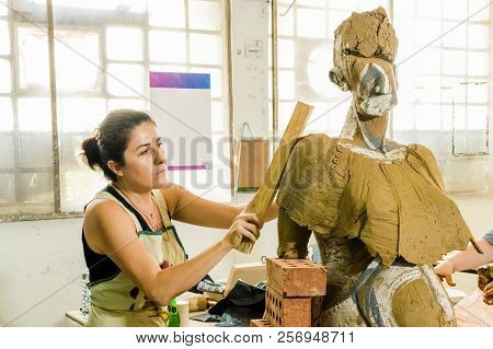 Beautiful brunette Caucasian artist working on her sculpture in an atelier poster