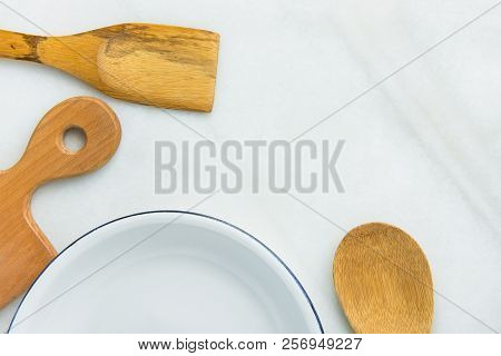 White Vintage Enamel Plate With Blue Edges Wooden Cooking Utensils On Marble Stone Background. Minim