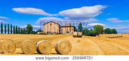 Beautiful countryside landscape with hay rolls and farm houses in Tuscany, Italy
