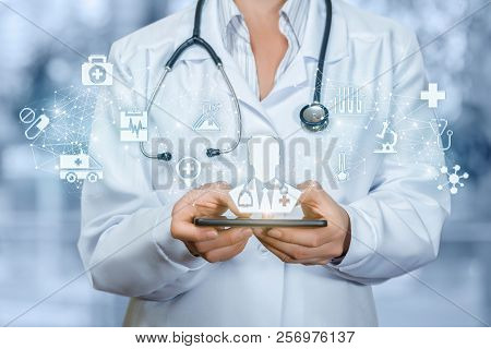 Mobile Service Concept. Doctor Holding Phone With Male Doctor On The Screen.