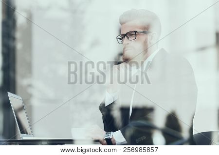 Serious Businessman Working Laptop Cafe Outdoors. Bearded Serious Man Wearing Suit And Glasses, Sitt