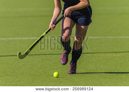 Hockey Action Abstract Photo Of Unidentified Girl Player Running Legs Ball And Stick On Astro Turf.