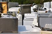 An image of old used appliances at a recycling facility. poster