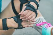 Woman rollerskater putting on wrist guards protector pads on her hand poster
