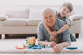 Portrait Grandpa and Grandson Playing with Toys. Family Relationship Between Grandfather and Grandson. Grandpa Teaching, Male Grandchild, Learning Concept. Relations and People Concept. poster