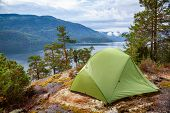 Camping tent at scenic wild campsite on a lake shore with mountain range in background - camping in Norway poster