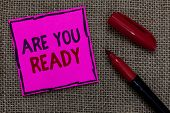 Word writing text Are You Ready. Business concept for Alertness Preparedness Urgency Game Start Hurry Wide awake Pink paper Important reminder Marker Communicate ideas Jute background. poster
