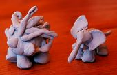 Tiny clay figures of porcupine or hegehog and elephant poster