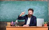 Telling educational stories. Teacher bearded man tell interesting story. Teacher charismatic hipster sit table classroom chalkboard background. Teacher interesting interlocutor as best friend poster
