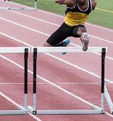 An African American high school track and field athlete racing over a hurdle. poster