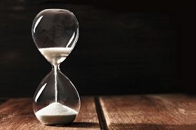 A Side View Of An Hourglass With Falling Sand, On A Dark Background With Copy Space