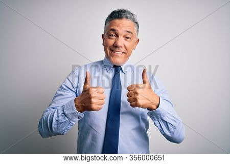 Middle age handsome grey-haired business man wearing elegant shirt and tie success sign doing positive gesture with hand, thumbs up smiling and happy. Cheerful expression and winner gesture.