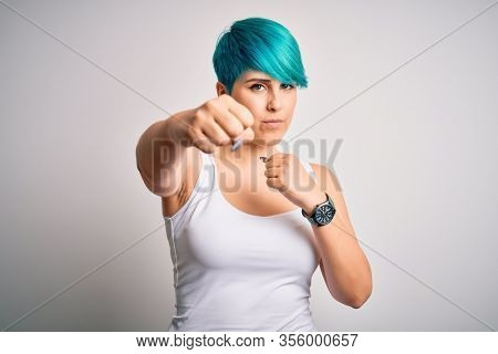 Young beautiful woman with blue fashion hair wearing casual t-shirt over white background Punching fist to fight, aggressive and angry attack, threat and violence