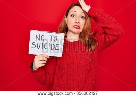 Beautiful redhead woman holding banner showing no to suicide message over red background stressed with hand on head, shocked with shame and surprise face, angry and frustrated. Fear and upset