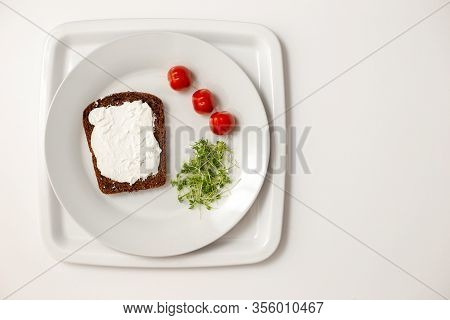 A Slice Of Bread, Spread With Cottage Cheese, Lies On A White Round Plate, Green Watercress And Red