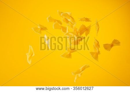 Zero Gravity Food Concept. Flying Uncooked Pasta On Yellow Background With Copy Space.