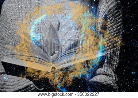 A Womans Hand Over A Magic Book On The Background Of The Starry Sky.the Concept Of The Spell Of Beau