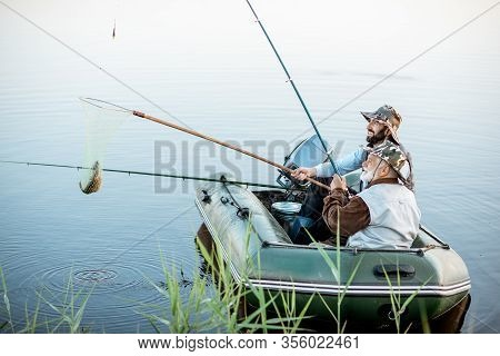 Grandfather With Adult Son Fishing On The Inflatable Boat, Catching Fish With Net On The Lake Early