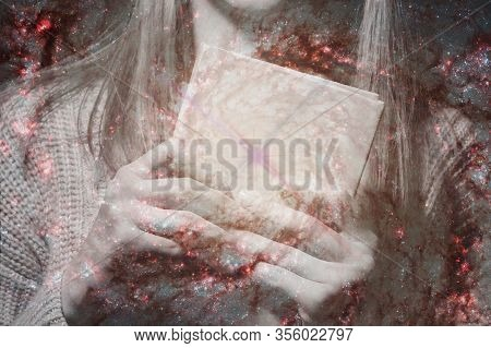Two Female Hands Holding A Magic Book On A Background Of The Starry Sky.the Concept Of The Spell Of