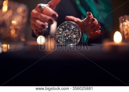 Hands of unrecognizable fortune-teller with ball of predictions