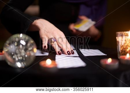 Fortuneteller's hands with cards at table with candles, magic ball in dark room