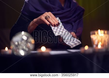 Close-up of female fortuneteller hand with cards while sitting at table with candles in dark room