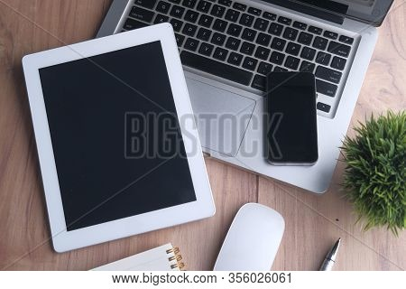 Top View Of Digital Tablet , Laptop, Smart Phone And Notepad On Orange Background