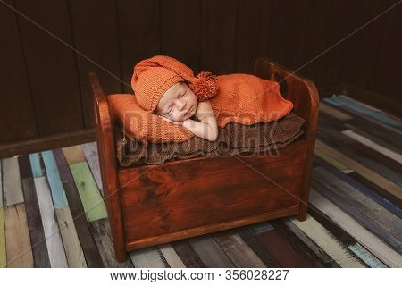 Cute Newborn Baby In Hat On A Brown Bed And Orange Pillow . Sleeping Baby On A Dark Background. Clos