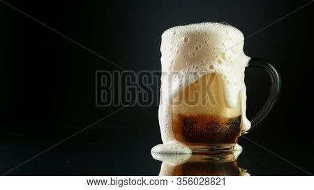 Beer foam overflowing from glass pint, isolated on black background